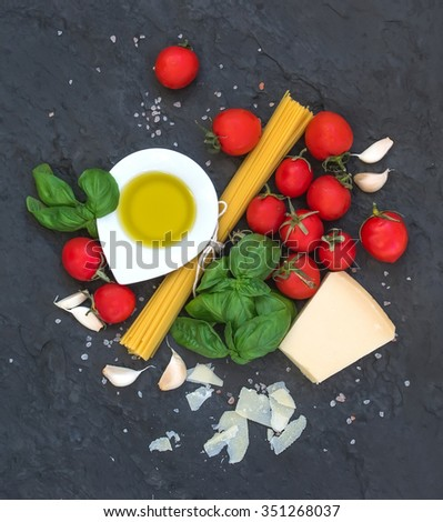 Ingredients for cooking pasta. Spaghetti, olive oil, garlic, Parmesan cheese, tomatoes and fresh basil on black slate background, top view - stock photo