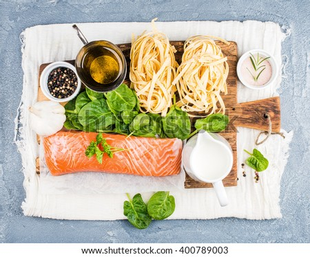 Ingredients for cooking pasta tagliatelle with salmon, spinach and cream on rustic wooden board over grey concrete textured background, top view, horizontal - stock photo