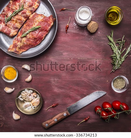 Ingredients for cooking raw lamb ribs in a pan with herbs, a knife, seasoning, tomatoes place for text,frame on wooden rustic background top view - stock photo