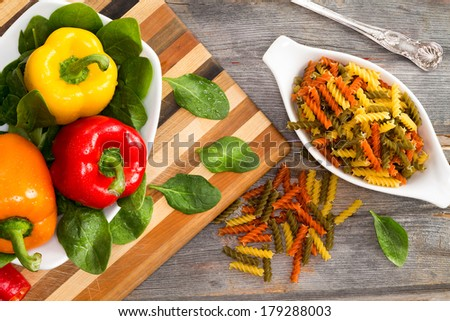 Ingredients for delicious fusilli pasta with an overhead view of fresh colorfrul sweet bell peppers in red yellow and orange on bed of baby spinach with dried corkscrews of tomato and spinach fusilli - stock photo