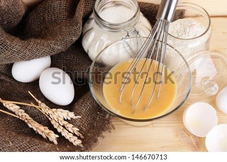 Ingredients for dough on wooden table on wooden background - stock photo