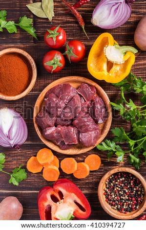 Ingredients for goulash or stew cooking: raw meat,herbs,spices,vegetables on dark wooden background, top view. - stock photo