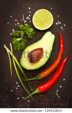 Ingredients for guacamole dip on a dark background. - stock photo