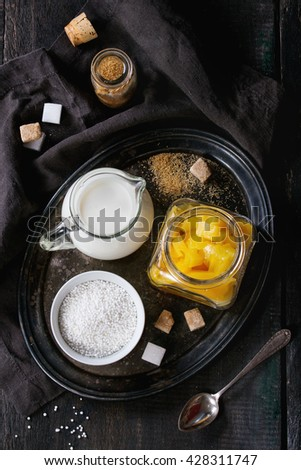 Ingredients for healthy tapioca pearls pudding dessert with coconut milk and mango. Served on vintage iron tray over old wooden table with black textile napkin. Dark rustic style, flat lay. - stock photo