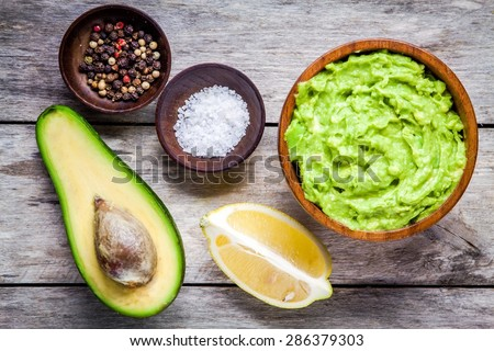 ingredients for homemade guacamole: avocado, lemon, salt and pepper top view - stock photo