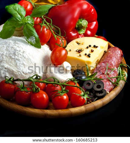 Ingredients for homemade pizza isolated in black - stock photo