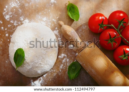 Ingredients for homemade pizza with a pile of bread dough for the base left to rise alongside fresh ripe red tomatoes and basil with a wooden rolling pin - stock photo