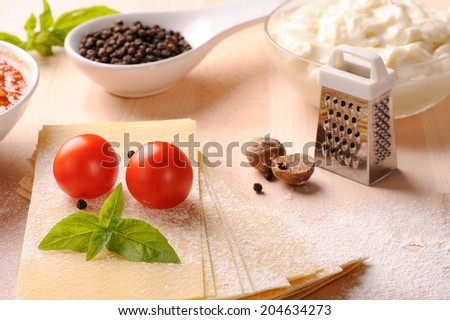 Ingredients for Italian lasagna with fresh cherry tomatoes and green basil leaves on sheets of dried pasta   - stock photo