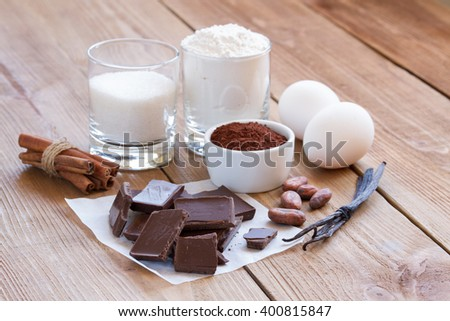 Ingredients for making chocolate chip cookies on a wooden background . Flour , sugar, egg ,  cocoa , cinnamon , vanilla and butter. Close up - stock photo