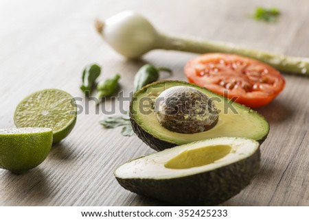 Ingredients for making guacamole on a wooden table - stock photo