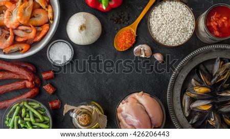 Ingredients for paella on the dark stone table horizontal - stock photo