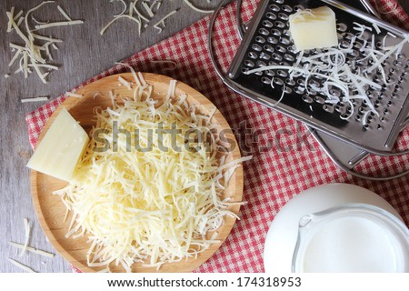 Ingredients for pasta cheese sauce or pizza, freshly grated parmesan or cheddar hard cheese, raw milk in a pot, kitchen tools, grater, wooden plate and kitchen towel, rustic vintage style - stock photo