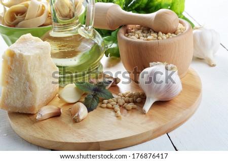 Ingredients for pasta pesto on white kitchen table - stock photo