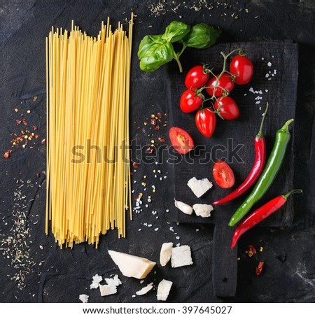 Ingredients for pasta sauce tomatoes, basil, garlic, chili peppers and parmesan cheese with dry spaghetti on wooden cutting board over black textured background. Top view. Square image - stock photo
