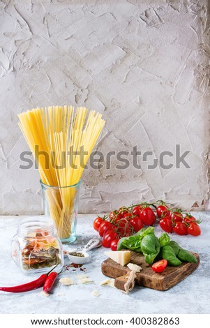 Ingredients for pasta sauce tomatoes, basil, garlic, chili peppers and parmesan cheese with dry spaghetti on wooden cutting board over white textured background.  - stock photo