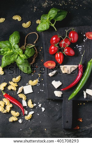 Ingredients for pasta sauce tomatoes, basil, garlic, chili peppers and parmesan cheese with dry creste di gallo pasta on wooden cutting board over black textured background. Top view - stock photo