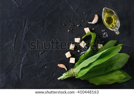Ingredients for pesto. Bunch of ramson, olive oil, parmesan cheese, garlic, salt and pepper over black textured background with copy space. Flat lay - stock photo