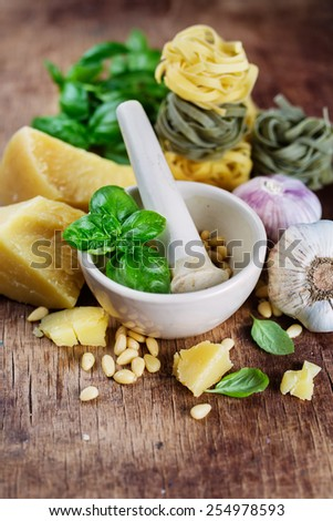 Ingredients for pesto, garlic, basil, pepper, cheese on white wood background - stock photo