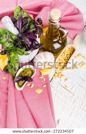Ingredients for pesto sauce: fresh basil, parmesan cheese, pine seeds and olive oil on wooden table. Selective focus - stock photo