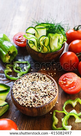 ingredients for quinoa salad with fresh tomatoes, cucumbers and cut green peppers on a dark rustic wooden table.selective focus. top view. - stock photo