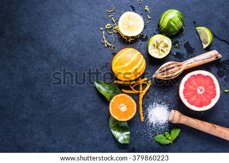 Ingredients for refreshing healthy lemonade, citrus fruits, zest on dark border background with space for recipe. - stock photo
