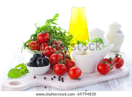 Ingredients for salad  with mozzarella, tomatoes,black olives,rocket and olive oil - stock photo