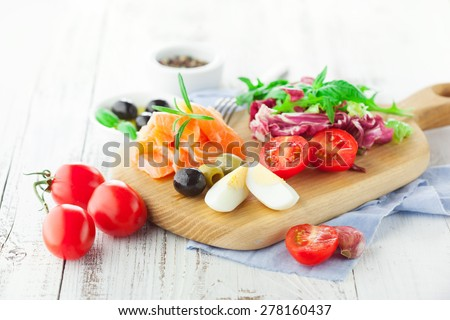 Ingredients for salad with salmon, cherry tomatoes and lettuce on a wooden chopping board on rustic white background, selective focus - stock photo