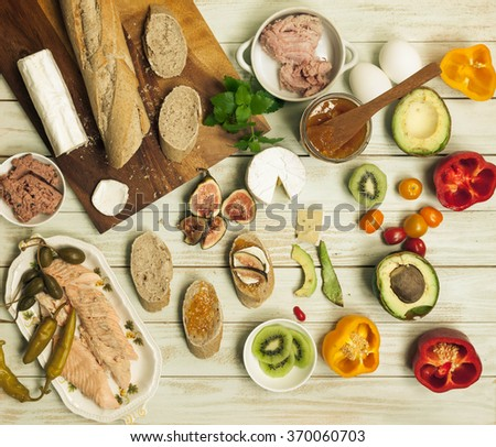 Ingredients for sandwich, build your own tartines, Small and simple cocktail snacks with various toppings, slices smoked salmon, boiled eggs, smoked meat, baguette. Top view, rustic style - stock photo