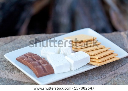ingredients for smores (marshmallow, graham crackers and chocolate) ready for cooking, shallow DOF - stock photo
