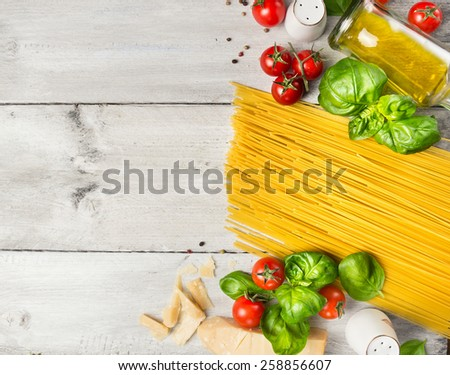 Ingredients for spaghetti cooking: tomatoes,basil,parmesan and oil on rustic wooden background, top view, place for text - stock photo