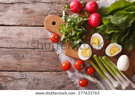 Ingredients for spring salad: eggs, sorrel, radishes, tomato. horizontal view from above  - stock photo