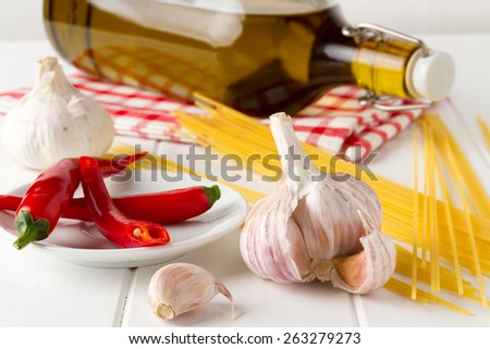 Ingredients for typical fast and easy italian food: Aglio olio e peperoncino, aromatic garlic, red chilli pepper, spaghetti, pepper and olive oil - stock photo