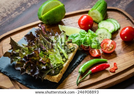 Ingredients for vegan / vegetarian sandwich with green pesto and fresh vegetables. Selective focus. - stock photo