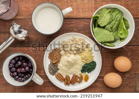 ingredients of healthy breakfast smoothie: almond milk, raw eggs, fresh spinach, frozen blueberries, whey protein, cacao, chia , pecans, maca root,  spirulina, spices with a  blender on rustic table - stock photo