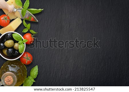 Ingredients of italian cuisine  - cherry tomato, basil, parmesan, olives  and olive oil - on dark background - stock photo