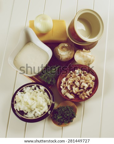 Ingredients of Mushroom Julienne with Raw Chopped Champignon Mushrooms, Onion, Dill with Bechamel and Cheese closeup on Plank White background. Retro Styled - stock photo