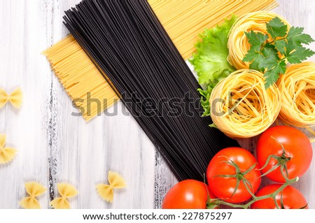 ingredients of pasta with tomatoes on a white wooden background - stock photo
