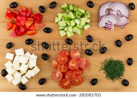 Ingredients prepared for Greek salad on bamboo board - stock photo
