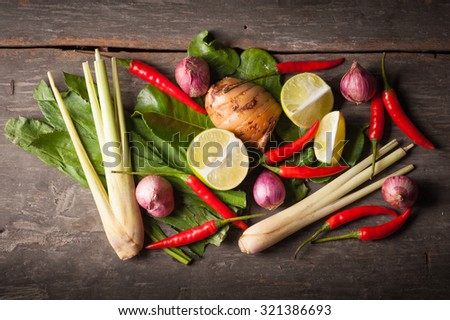 Ingredients set for Thai spicy soup (Tom-yum) include lemon, galangal, red chili, red onion, lemongrass, and kaffir lime leaf on wood table in morning scene - stock photo