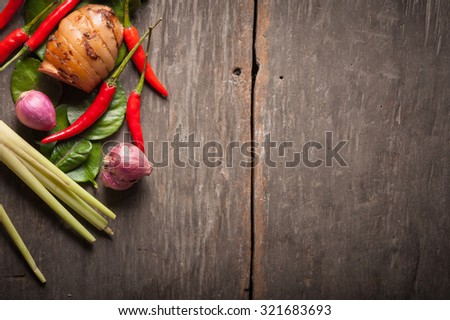 Ingredients set for Thai spicy soup (Tom-yum) include lemon, galangal, red chili, red onion, lemongrass, and kaffir lime leaf on wood table in morning scene with blank area for text or message - stock photo
