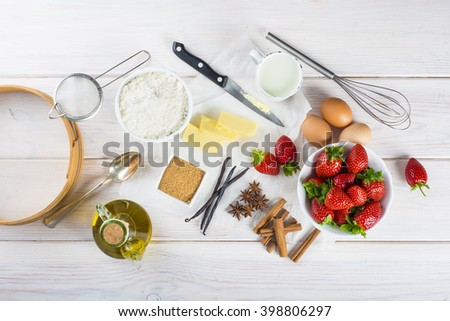 Ingredients to cook an strawberry cake on the table of the kitchen - stock photo