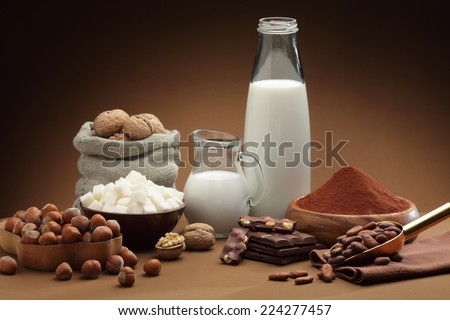 Ingredients to make chocolate: cocoa beans, milk, nuts, sugar, cocoa powder - stock photo