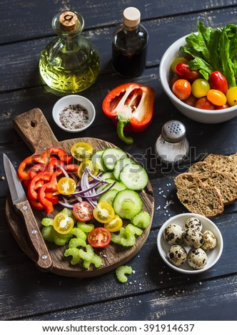 Ingredients to prepare vegetable salad - tomatoes, cucumber, celery, bell pepper, red onion, quail eggs,olive oil, balsamic vinegar, garden herbs and spices on a rustic wooden board. Healthy food - stock photo