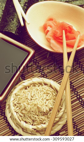 Ingredients to Preparing Sushi  with Nori, Ginger, Rice, Soy Sauce and Chopsticks on Bamboo Straw Mat. Retro Styled - stock photo
