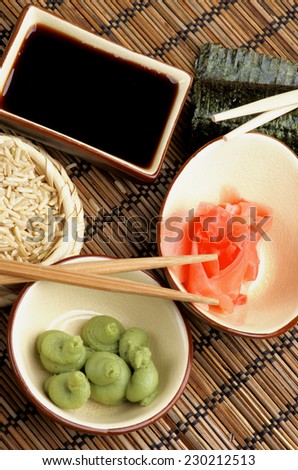 Ingredients to Preparing Sushi  with Nori, Ginger, Wasabi, Rice, Soy Sauce and Chopsticks on Bamboo Straw Mat - stock photo