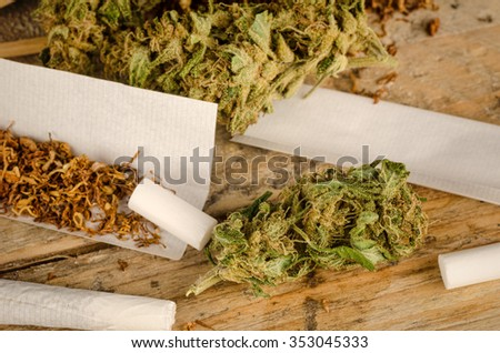 Ingredients to roll a joint on a rustic wooden table - stock photo