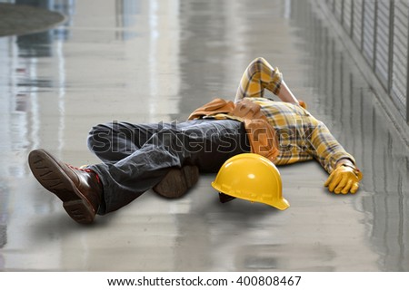 Injured construction worker laying on floor after fall - stock photo