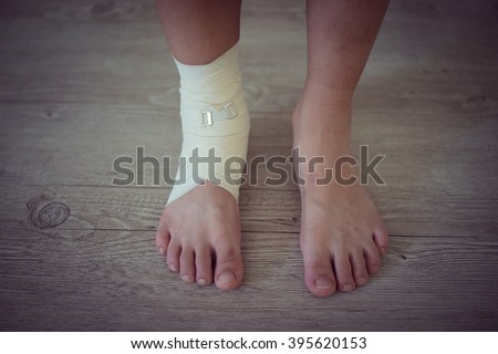 Injured foot on a wooden floor background - stock photo