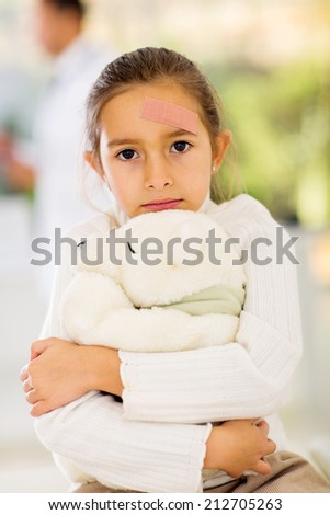 injured girl with band-aid on her forehead in hospital - stock photo