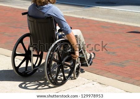 Injured male veteran sitting in his wheelchair rolls on the sidewalk. - stock photo